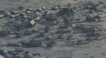 Overlooking Coastal Village Among Rugged Snowy Arctic Landscape