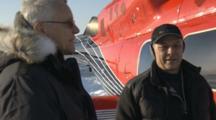 Men Talk Outside Helicopter On Snow Field