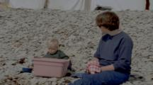 Woman With Toddler Wash Dishes On Rocky Beach