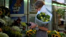 Woman Buys Flowers From Vendor In Market