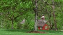 Red Farmhouse Among Green Foliage