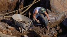 Workman Putting Rocks In Wheelbarrow