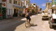 Man Rides Bike Down Small Town Street