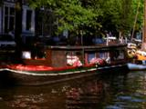 Cruising Down Canal Past Houseboat With Flowers