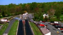 Motorcycle Drivers Race Down Track With Forest In Background  - Aerial To Landscape With Trees And Buildings