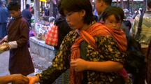 Woman With Baby At The Marketplace Purchasing Goodies