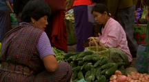 Female Customers Buy Vegetables At Stand In Marketplace