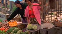 Woman Weighs Produce At The Marketplace