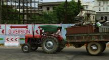 Men Drive Tractor, Trailer Past Construction Site