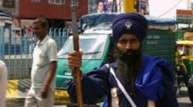 Man In Uniform Poses With Sword On Busy Street