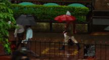 Pedestrians Walk Down Street In Rain