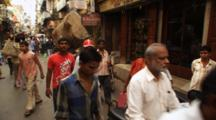Pedestrians Walk In Crowded Market, Man Carries Heavy Load