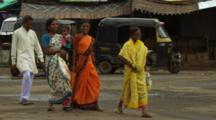 Women In Saris Walk Down Busy Street