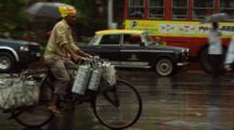 Man Carries Goods On Bicycle On Rainy Street