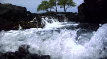 Slow Motion Waves Splash Onto Black Rocks