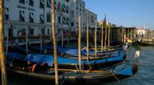 Gondolas Tied Up Along A Canal