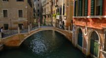 People Walk Over Small Bridge In Venice