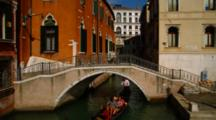 Gondola Passes Under Small Bridge In Venice