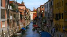 Gondola Travels Down A Colorful Venice Canal
