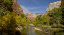 River Flows Below Sandstone Cliffs In Zion National Park