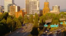 Traffic On Freeway Below Portland, Oregon Skyline At Sunset