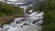 Cascades From Mountain Stream Flow Over Rocky Terrain