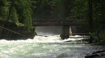 People Stand On Footbridge Over Fast Creek