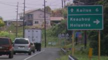 Cars Passing Highway Signs In Kona, Hawaii, Pointing To Kailua, Keauhou, And Holualoa. House Beside Road In The Distance.