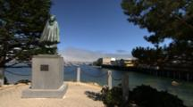 Jeremy Lucido Statue In Foreground. Monterey Wharf And Harbor In Background