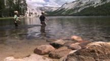 Two Boys Wading Across Tenaya Lake In Yosemite National Park
