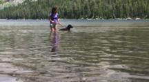 Woman Wading With Her Black Lab In Tenaya Lake, Yosemite National Park