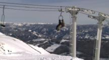 People Ride On Ski Lift With Mountain Range Behind