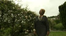 Woman Walks By Rose Pergola At Hotel Endsleigh In English Countryside