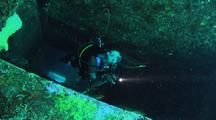 Female Diver Inside Wreck With Torch