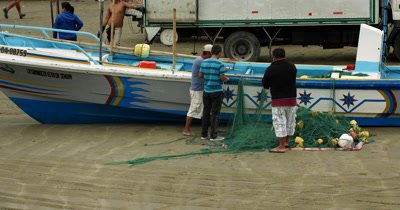 Medium Shot of Fishermen repairing their fishing nets next to their boat, at Puerto Lopez fish market .