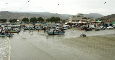 Pan from the town of Puerto Lopez, past the fish market to the harbour.