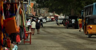 Medium Shot of a main Street in Puerto Lopez, with many Tuk Tuk's as a common form of transportation.