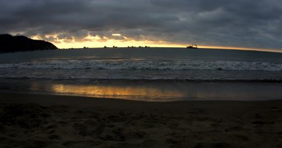 Wide Shot of a Sunset off the beach of Puerto Lopez, with the silhouettes of fishing boats on the horizon