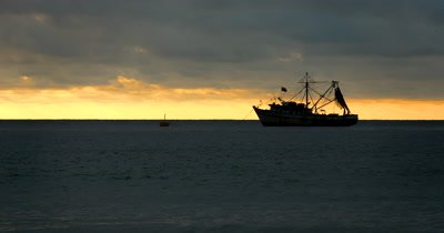 Medium Shot of a Sunset off the beach of Puerto Lopez, with the silhouettes of a fishing boats.