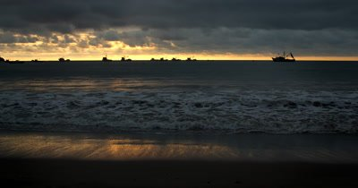Wide Shot of a Sunset off the beach of Puerto Lopez, with the silhouettes of Five fishing boats on the horizon