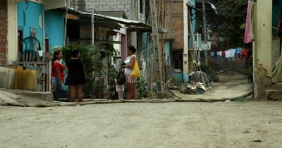 Wide shot of a Street in the village of Puerto Lopez, with a Tuk Tuk driving down the street.