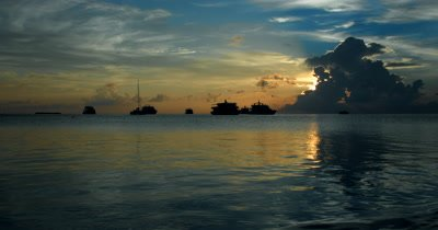The sun setting behind storm clouds over the sea with blue sky above and yachts resting in the calm water.