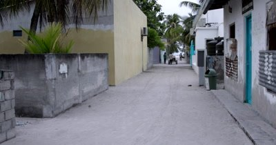 Long shot of Mathiveri Island village sandy street showing homes and people going about their daily work