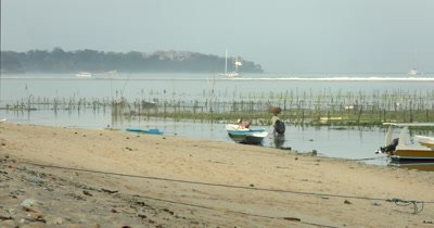 Wide shot of two seaweed farmers heading out to work, carrying their basket and tube.