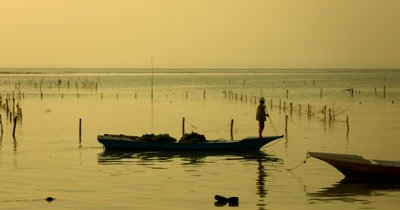 Medium Shot, during a golden Sunset, of a  Seaweed Farmer, heading back home, in their traditional boat after harvesting.