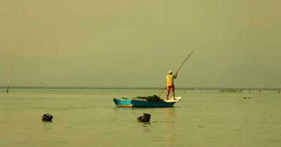 Medium Shot  of a  Seaweed Farmer heading back home,in their traditional boat, after harvesting.