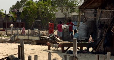 Wide shot of two villagers collecting recyclable plastic into huge bags.