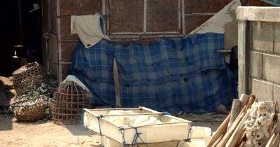 Medium shot across a village home down between two shacks.