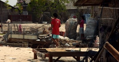 Wide shot of Three villagers collecting  plastic and metal for recycling.