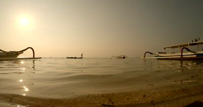 Wide Shot, during a golden Sunset, of a  Seaweed Farmer, heading back home, in their traditional boat after harvesting.